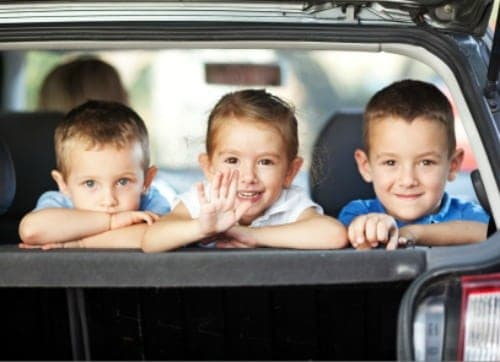 Three children waving from the back of a car