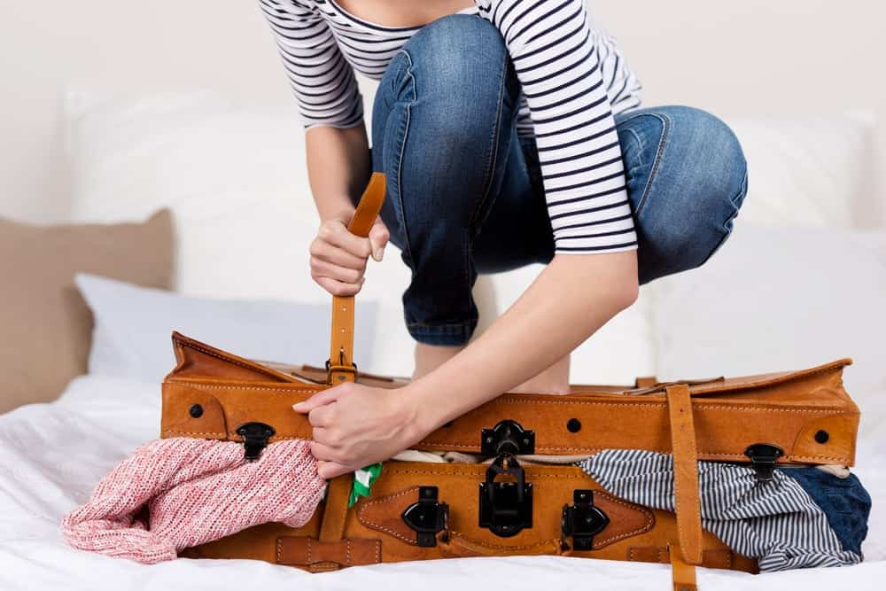 woman trying to close suitcase overflowing with clothes
