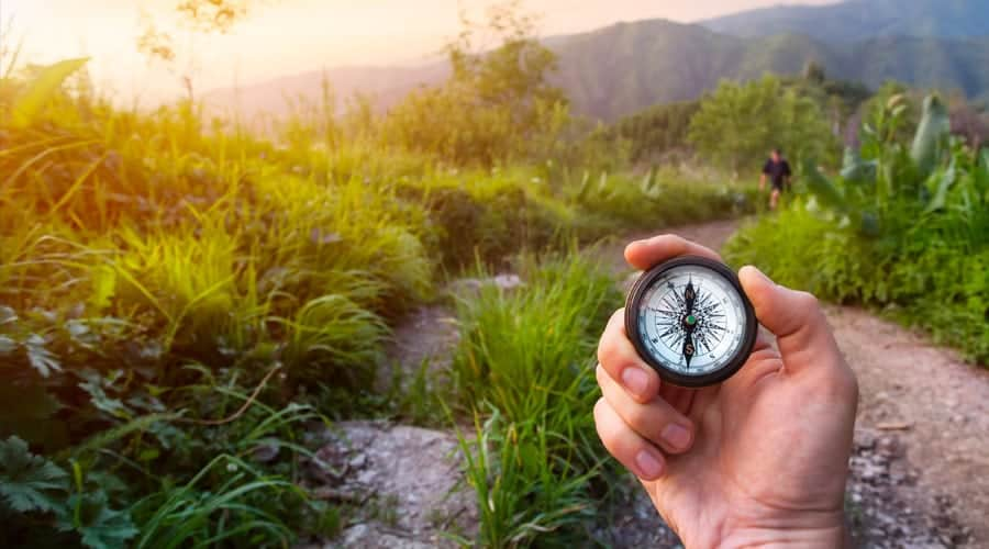 a hand holding a compass on a mountain trail in the Smoky Mountains