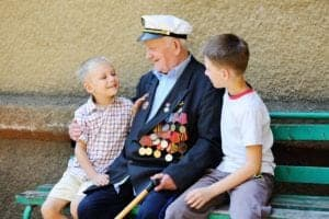 Veteran sitting on bench with children